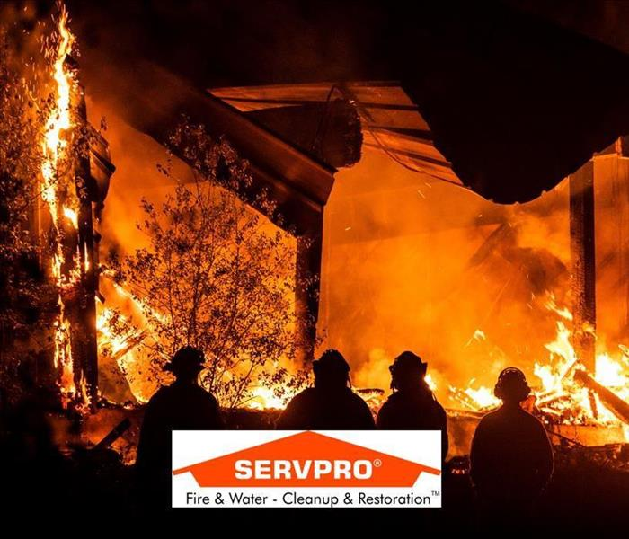 The outside of a house that is caught on fire with flames rising and firefighters putting it out and the SERVPRO logo