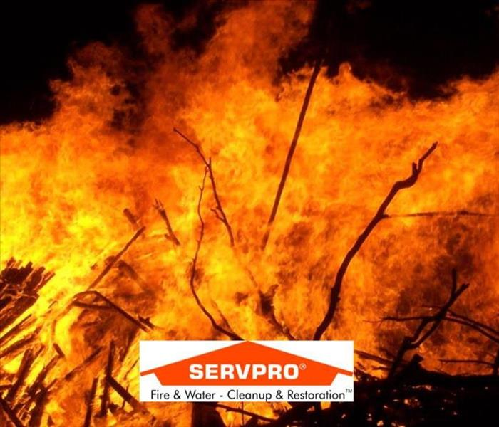An image of a man made fire with twigs and the SERVPRO logo
