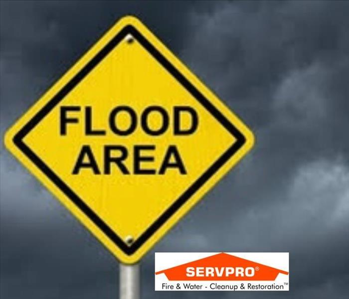 A close up picture of a yellow street sign that says flood area on it and the SERVPRO logo at the bottom
