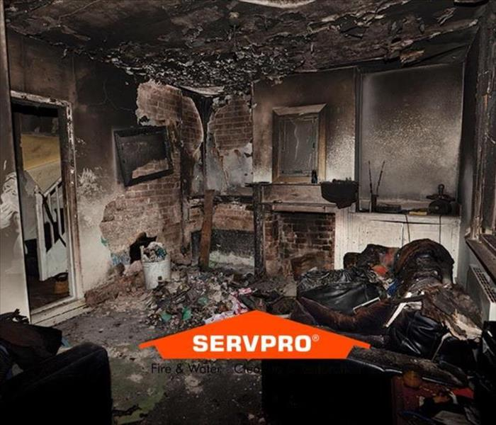 A dark room full of burnt objects caused by a fire with the SERVPRO logo at the bottom center