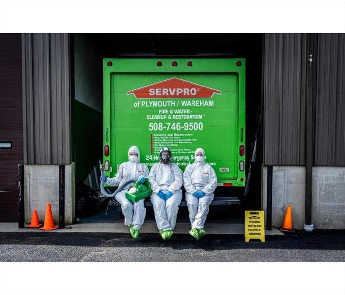Three people in white Tyvek suits with blue gloves & black respirators on they have yellow boots on & the SERVPRO logo