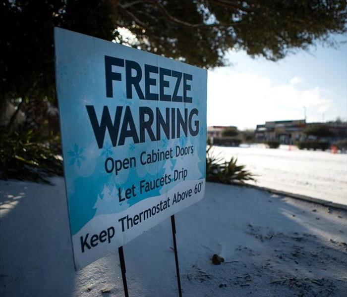 A blue freeze warning sign buried in snow