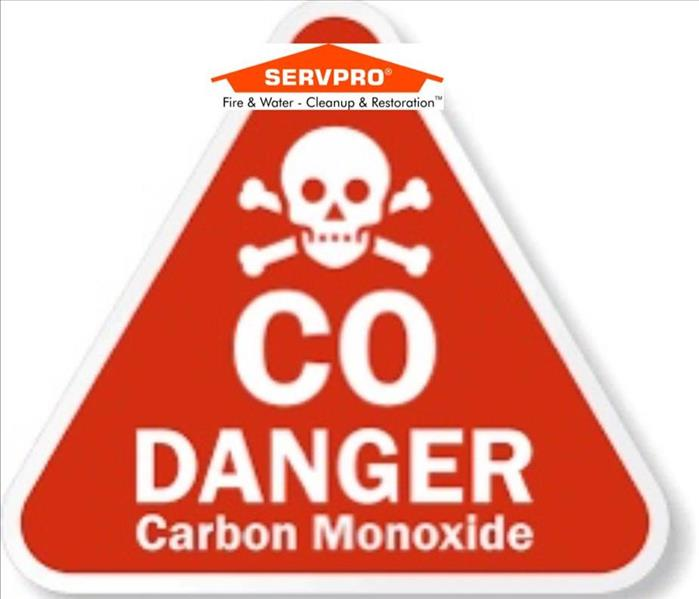 "A red triangle with a white skull and cross bones and the words ""CO DANGER Carbon Monoxide"" with the SERVPRO logo at the top"