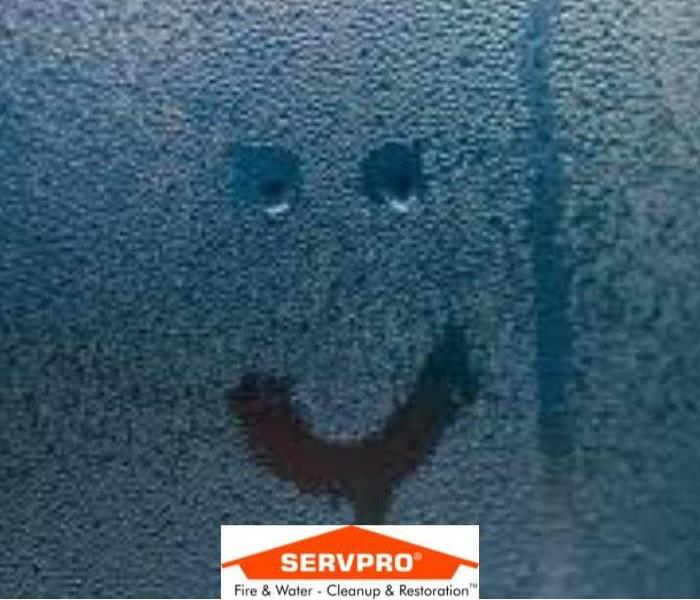 A bathroom shower wall that has condensation on it and a smiley face drawn on it and the SERVPRO logo at the bottom