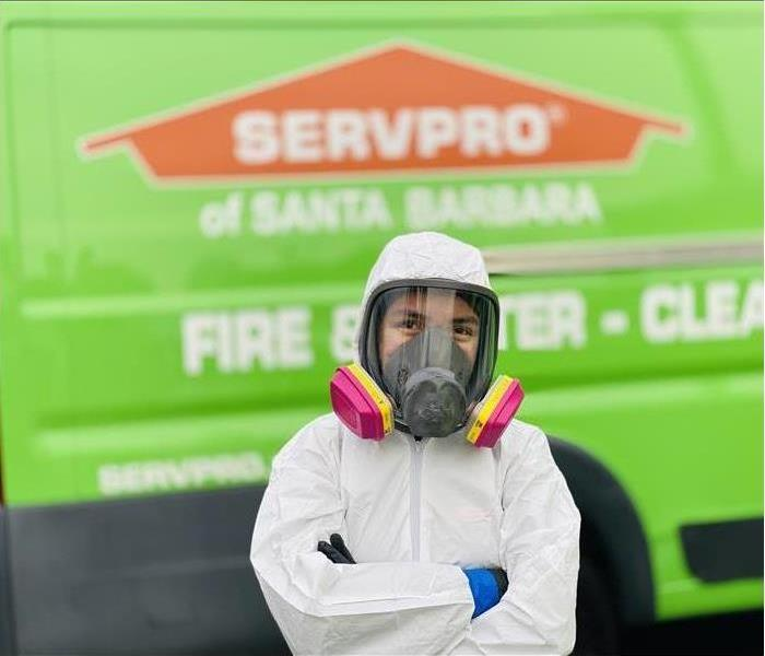 A SERVPRO employee in a white suit and a pink mask